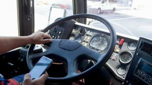 close-up of a truck driver holding a cell phone and typing on i