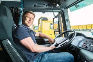 fleet driver sitting behind the wheel of a truck smiling