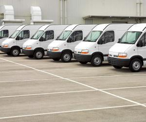A row of white fleet vans in a parking lot.